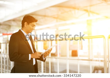 Indian business man using tablet computer while waiting train at railway station, golden sun background. - stock photo