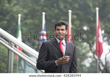 Indian business man with a Smart Phone, in front of flags. Portrait of an Asian businessman smiling, holding a Smart Phone, in front of flags. Global business concept. - stock photo