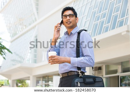 indian business man with smart phone with office background - stock photo
