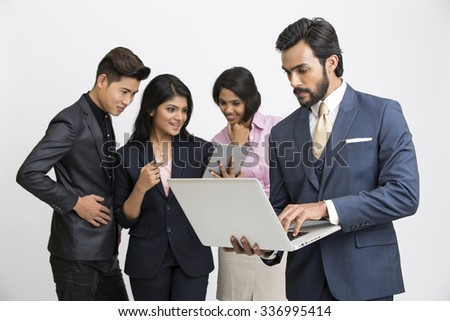 Indian business people busy working with their team leader on white background. - stock photo