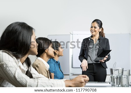 Indian business woman giving presentation with her digital tablet. - stock photo