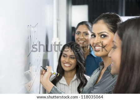 Indian business woman writing on a whiteboard with her team around her. - stock photo