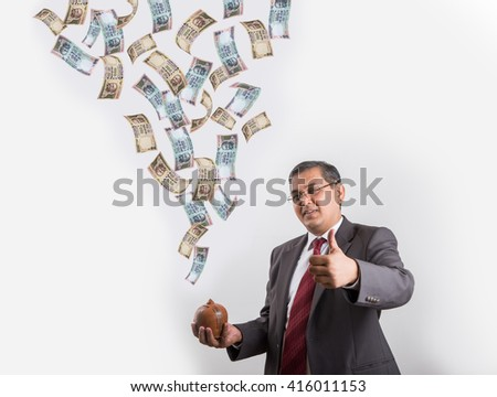 indian businessman catching flying currency in his piggy bank made up or clay, happy asian businessman with piggy bank under falling indian currency notes