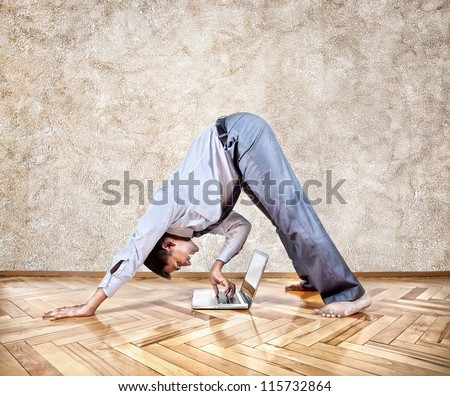 Indian businessman doing yoga and typing on his laptop in the office at brown background - stock photo