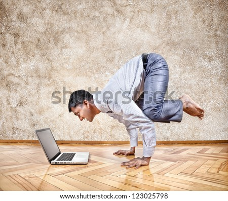 Indian businessman doing yoga hand stand pose and looking at his laptop in the office at brown textured background - stock photo