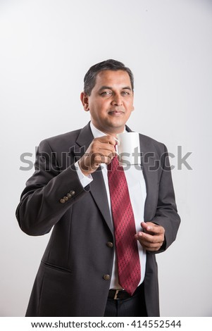 indian businessman having coffee or tea, asian businessman and coffee or tea, businessman drinking coffee in big white cup, isolated over white background, front view