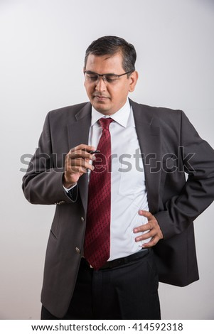 indian businessman holding ball pen and thinking, indian businessman thinking, asian businessman holding pen while deep thinking, indian businessman solving problem, isolated over white background - stock photo