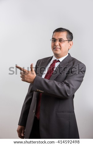 indian Businessman isolated over white background presenting copy space. asian Happy business man giving presentation on copy space, Happy business man giving presentation on white background - stock photo