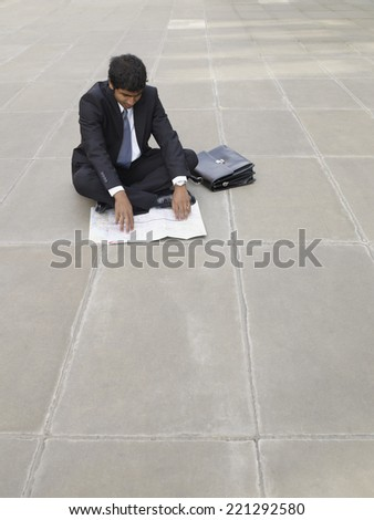 Indian businessman looking at map - stock photo