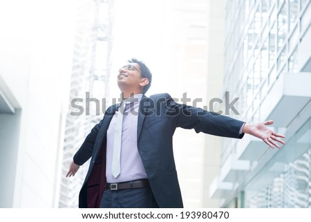 Indian businessman open his arms wide, looking up into the light, modern office building as background, natural sunlight. - stock photo