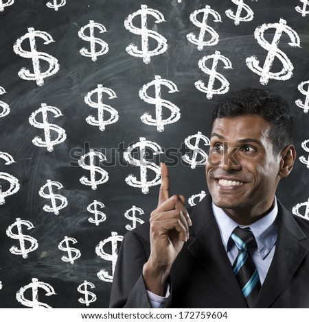 Indian businessman pointing upwards at dollar signs written on chalk board. The photo has been composed so there is plenty of space for your message. - stock photo