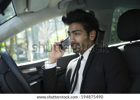 Indian businessman sitting in his car and talking on mobile phone.