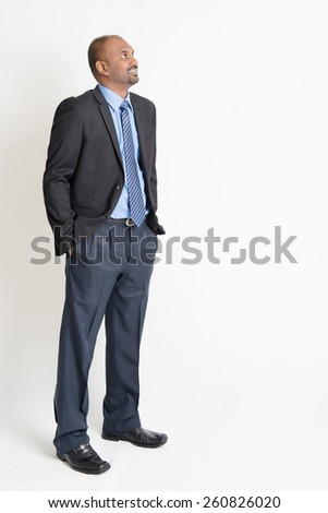 Indian businessman smiling and looking away towards copy space, full body standing on plain background. - stock photo