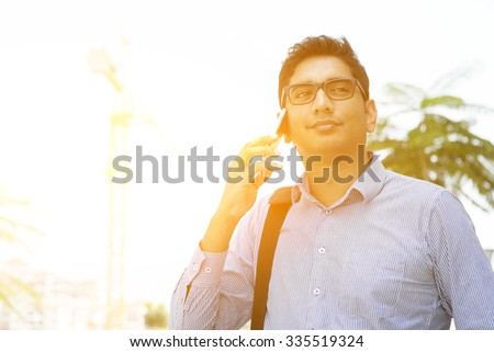 Indian businessman talking on phone in front modern office building. City view with beautiful sunlight. - stock photo