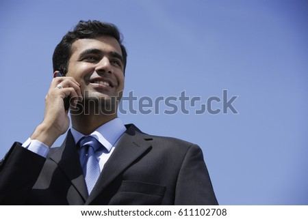 Indian businessman talking on phone outside.
