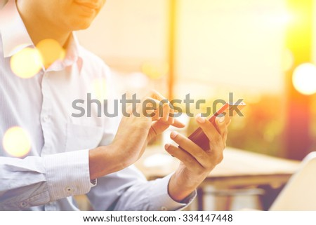 Indian businessman using smartphone at outdoor cafeteria, beautiful blurred golden sunlight at back. - stock photo