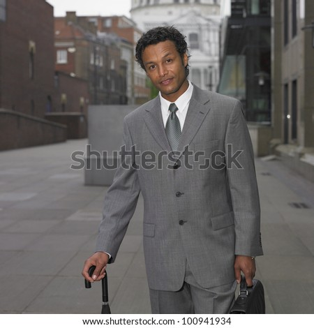 Indian businessman with umbrella in urban area