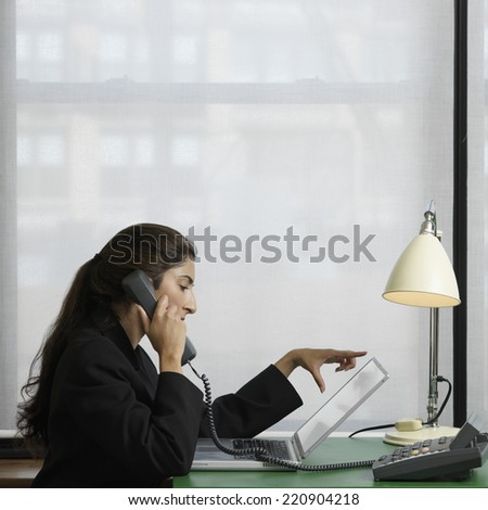 Indian businesswoman talking on telephone - stock photo