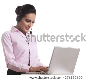 Indian businesswoman using headset and laptop against white background - stock photo