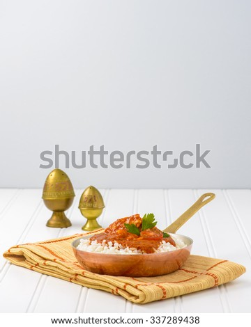 Indian butter chicken served on top of white rice. - stock photo