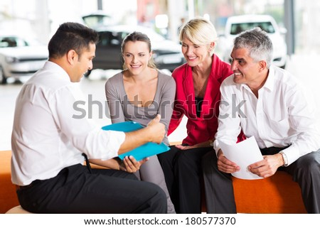 indian car dealer explaining sales contract to the family buying a car - stock photo