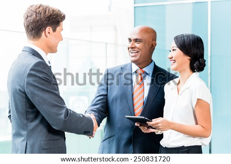 Indian CEO and Caucasian executive having business handshake in front of city skyline - stock photo