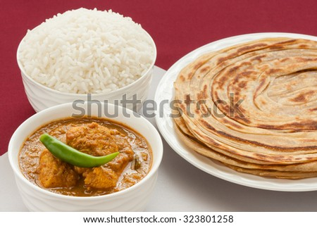 Indian chicken curry meal - Closeup view of Indian chicken curry meal with rice and wheat parotta (Indian bread). Green chilli used as garnish. Natural light used. - stock photo