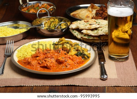 Indian chicken curry meal with beer - stock photo