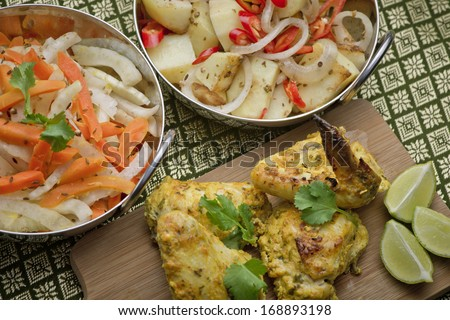 Indian chicken on a platter with bowls of salad and a garnish of lime, corriander and chili - stock photo