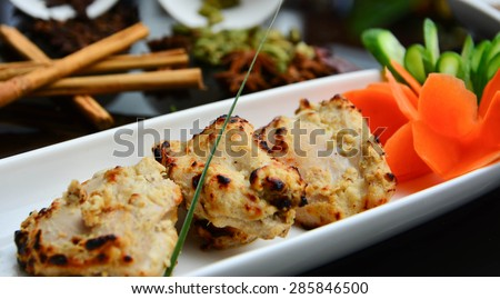 Indian chicken pieces main dish served with carrot and cucumber - stock photo