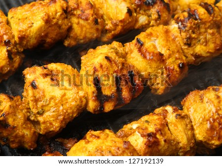 Indian chicken tikka kebabs cooking on griddle plate.