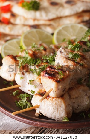 Indian chicken tikka kebabs on skewers macro on a plate. vertical - stock photo