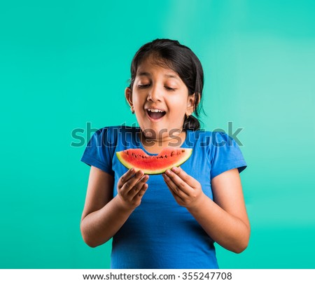 indian child girl eating watermelon isolated on green background, asian girl with a portion of the watermelon in her hands, small girl holding watermelon, girl with black hair and watermelon, - stock photo