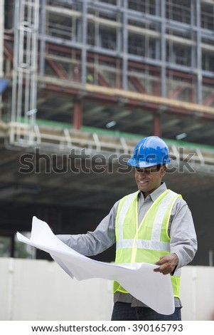 Indian construction manager or Architect checking the blueprint plans at a building site.