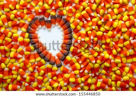 Indian corn heart on candy corn candies background - stock photo