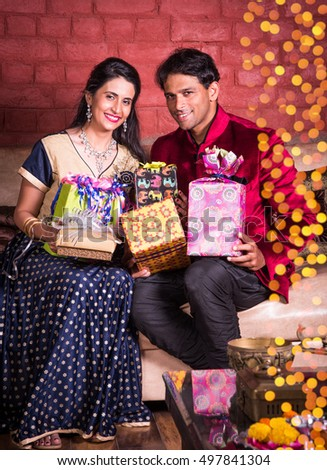 indian Couple exchanging or holding diwali gifts / presents while sitting on a sofa or couch on diwali night