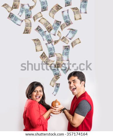 indian couple excited to see currency notes falling in clay money box, asian couple holding piggy bank and money falling into it, indian currency flying, indian rupee falling - stock photo