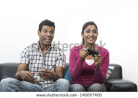 Indian couple, man and woman, having fun playing video console games together. - stock photo