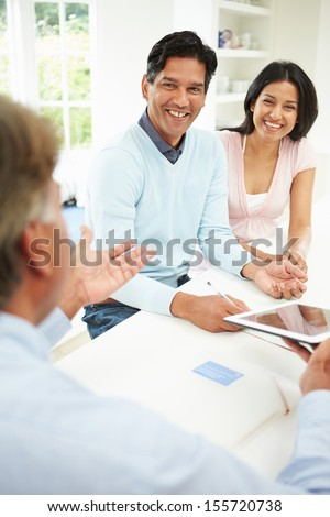 Indian Couple Meeting With Financial Advisor At Home - stock photo