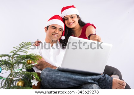 Indian couple sitting on couch with christmas tree, celebrating christmas wearing santa hat, busy in online festival shopping or surfing, asian couple and christmas, closeup on white background - stock photo