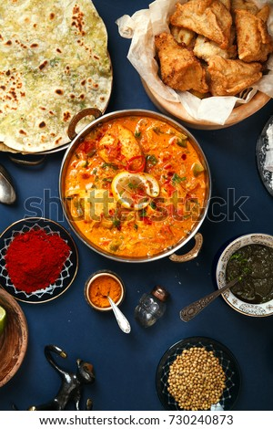 Indian cuisine on diwali holiday: tikka masala, samosa, patties and sweets with mint chutney and spices. Dark blue background. Vertical composition