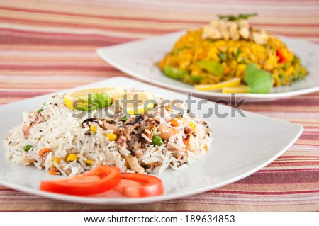 Indian cuisine - Rice with seafood - Rice with seafood with lemon and tomatoes on white plate and rice with chicken white meat in background on canvas