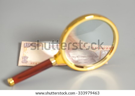 Indian Currency Rupee Note with magnifying glass  on gray background