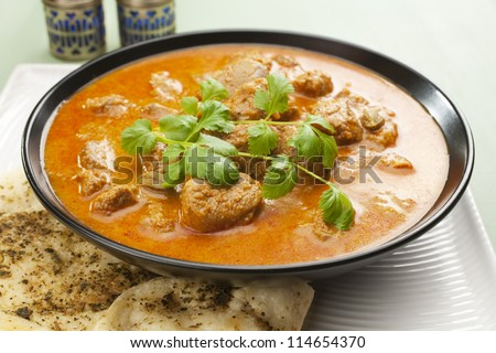 Indian curry lamb rogan josh in a black bowl, with naan bread. - stock photo