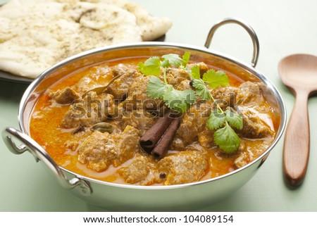 Indian curry lamb rogan josh in a steel karahi, with naan bread. - stock photo