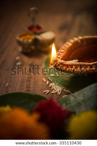 Indian decorative traditional clay lamp burning in the pooja set up. Selective focus treatment - stock photo
