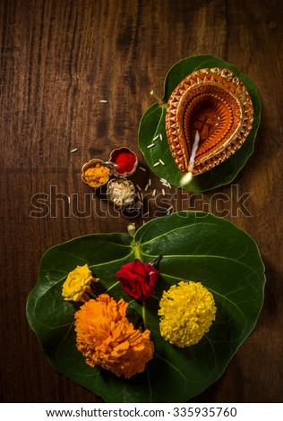 Indian devotional or puja material and objects. Ghee lamp, fresh flowers and kumkum tilak. View fro top. - stock photo