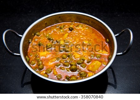 Indian dish green gram with tomato curry and potatoes purely vegetarian, spicy and delicious shot on black granite slab - stock photo