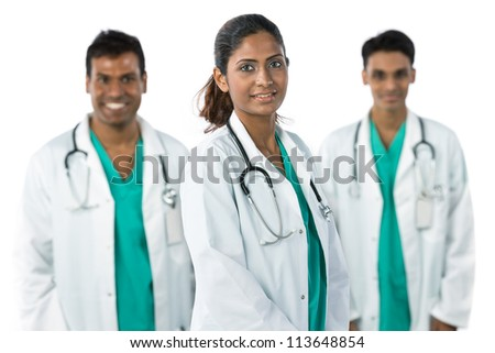 Indian doctor wearing a white coat with stethoscope. Her team are out of focus in background. - stock photo