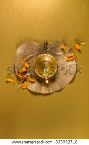 Indian earthen lamp on golden dry leaf with scattered marigold flower petals. view from above. Diwali greeting card cover. - stock photo
